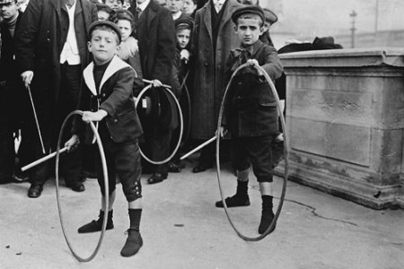 rolling a hoop and stick toy down the street