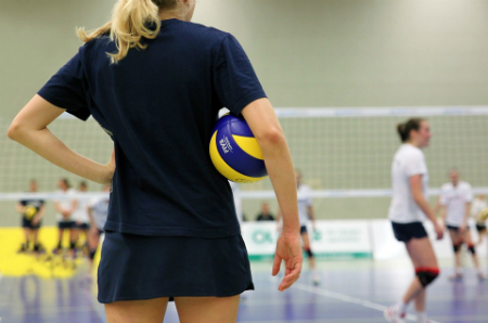 A volleyball player stands on the side of the court with a volleyball tucked under her arm