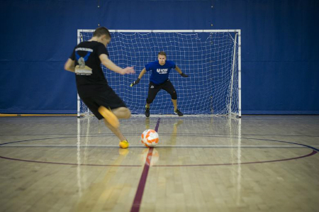 A futsal player shoots the ball at the goal guarded by a goalie