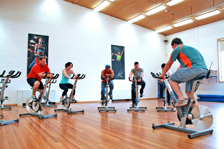 A cycling class in a studio with the instructor in the front of the class