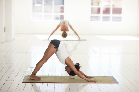 Two women in an open studio practicing yoga