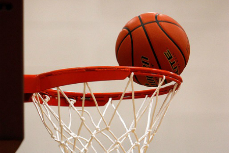 A basketball barely misses the rim as the ball sails into the net