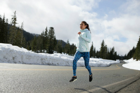 A woman running on the side of the road while the area around her is surrounded by trees and snow