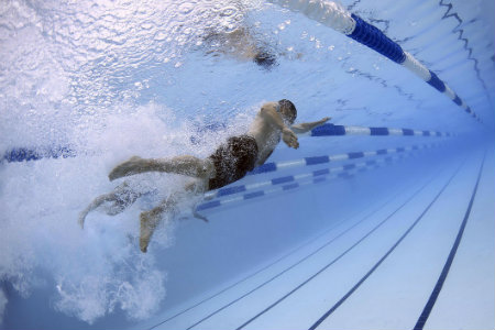 a man swims freestyle while doing laps in the pool