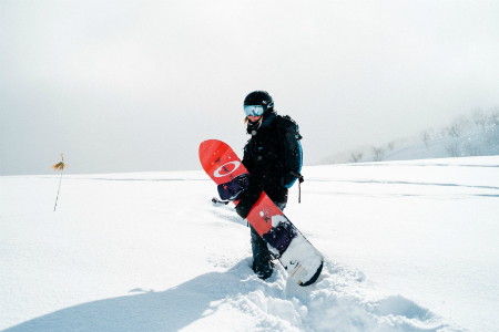 Girl standing in the snow with her snowboard smiling