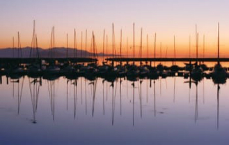 The Great Salt Lake at sunset with sailboats docked in a marina
