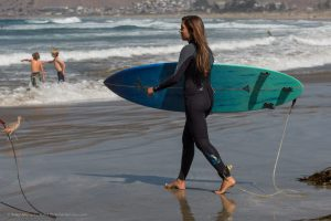 """Female teen holding turquoise blue surf board with leash entering water with friends.  People, on Morro Strand State Beach, Morro Bay, CA.  A sunny warm, late summer day, with a number of visitors and families enjoying the sun, sand, and surf just north of Morro Rock.  07 October 2012.   Photo © 2012 """"Mike"""" Michael L. Baird, mike {at] mikebaird d o t com, flickr.bairdphotos.com, Canon 5D Mark III, with Canon EF 100-400mm f4.5-5.6L IS USM Telephoto Zoom Lens, with circular polarizer, handheld, IS, RAW.  Aperture Priority, ISO 400. See EXIF for obtained shutter speed.  GPS encoding and compass direction was realtime from an on-camera Canon GP-E2 GPS Receiver.  To use this photo, see access, attribution, and commenting recommendations at http://www.flickr.com/people/mikebaird/#credit - Please add comments/notes/tags to add to or correct information, identification, etc.  Please, no comments or invites with badges, images, multiple invites, award levels, flashing icons, or award/post rules.   Critique invited."""