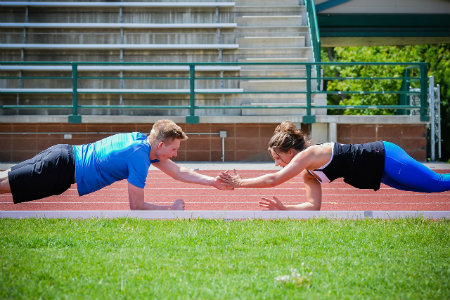 a male and female couple take part in an exercise buddy routine